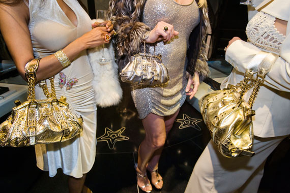 Lauren Greenfield: Jackie, 41, and friends with Versace handbags at a private opening at the Versace store, Beverly Hills, 2007.  A Versace devotee, Jackie shopped from monthly shipments of new merchandise that the design house sent to her home. Credit: Lauren Greenfield/INSTITUTE © Lauren Greenfield