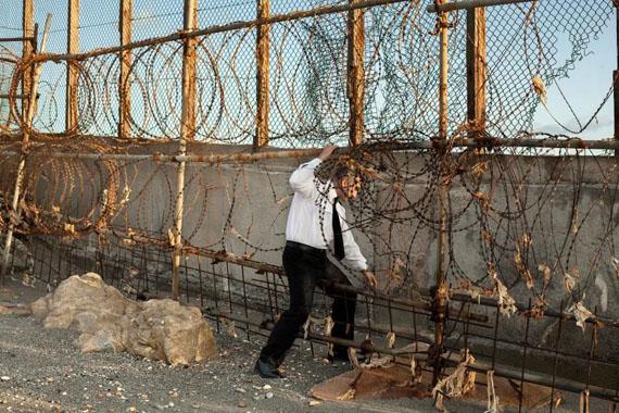 Arnau Bach, La barrière de Gibraltar, Territoire britannique d'outre-mer de Gibraltar, 2016.Un douanier britannique inspecte le trou découpé par des trafiquants de tabac dans la barrière frontalière qui sépare le Royaume-Uni de l'Espagne le 10avril 2016. Gibraltar est un territoire britannique d'outre-mer situé à la pointe sud de la péninsule ibérique.Avec l'aimable autorisation de l'artiste.