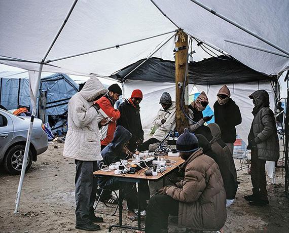 Station de recharge des téléphones, bidonville d'état pour migrants, Calais, 2015 © Bruno Serralongue