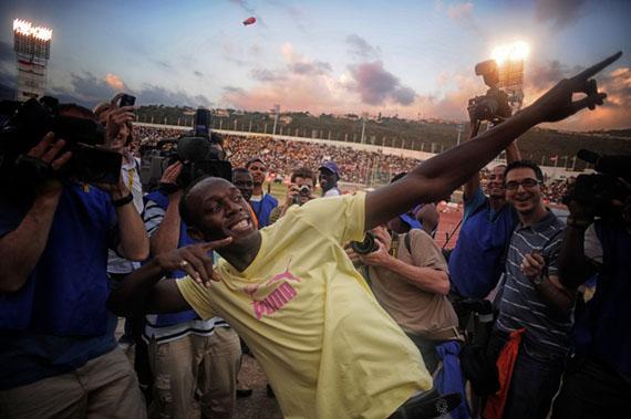 """Usain Bolt – Weltbester Sprinter, er zeigt seinen """"bow"""" und alle sind begeistert. Boys and Girls Championships im Nationalstadion in Kingston/Jamaika. April 2009, © Harald Schmitt"""