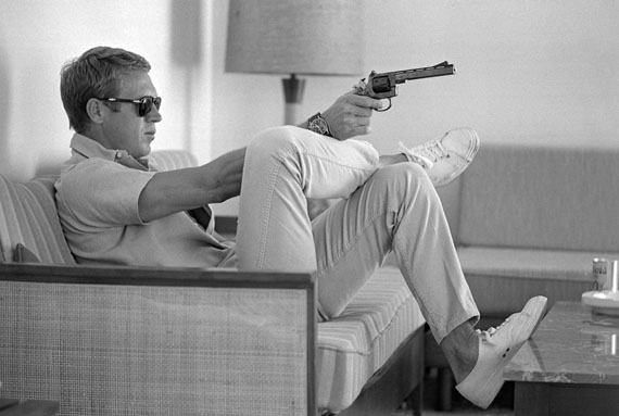 Steve McQueen aims a pistol in his living room, California 1963. © John Dominis / Time Inc. All Rights Reserved.